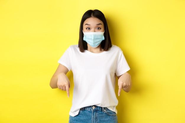 Covid-19, pandemie en concept voor sociale afstand. verbaasde aziatische vrouw met medisch masker, die reclame toont, naar rechts wijst en glimlacht, gele achtergrond.
