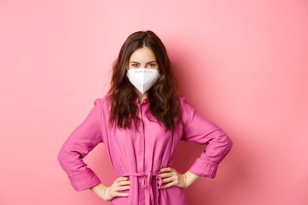 Covid-19, pandemie en levensstijlconcept. boze vrouw in medisch gasmasker kijkt met oordeel en afkeer, fronst en scheldt iemand uit zonder gezichtsmasker, roze muur.