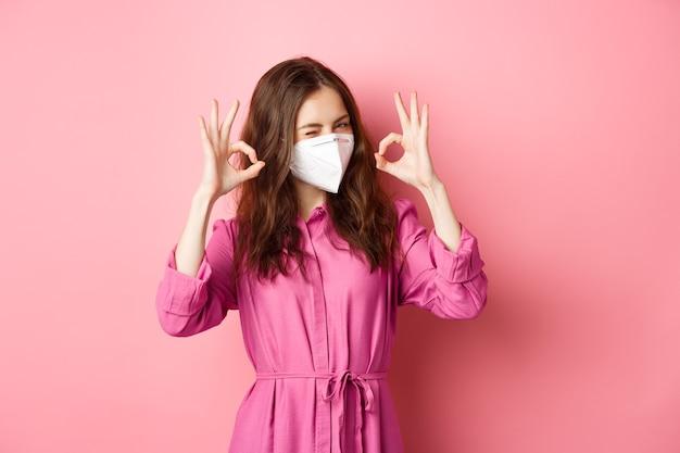 Covid-19, pandemie en levensstijlconcept. vrolijk meisje toont goed teken, draagt medische gasmasker als preventieve maatregel tegen corona, roze muur. kopieer ruimte