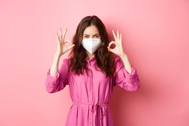 Covid-19, pandemie en levensstijlconcept. vrolijk meisje toont goed teken, draagt medische gasmasker als preventieve maatregel tegen corona, roze muur.