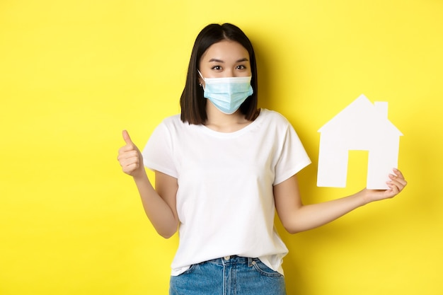 Covid-19, pandemie en onroerend goed concept. de vrij aziatische vrouw die in medisch masker glimlacht, document huisknipsel en duim toont, keurt goed en houdt van agentschap voor het kopen van bezit.