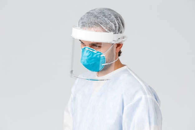 Covid-19, pandemie, gezondheidswerkers die een virusuitbraak bestrijden. profiel van een vermoeide jonge arts in persoonlijke beschermingsmiddelen, pbm-pak en medisch masker, kijkend naar patiënt met symptomen van coronavirus