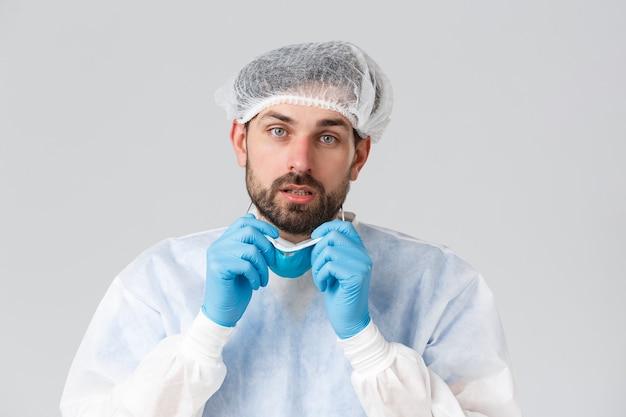 Covid-19, pandemie, gezondheidswerkers die een virusuitbraak bestrijden. vermoeide bebaarde arts die een medisch ademhalingstoestel opstijgt, persoonlijke beschermingsmiddelen draagt, camera kijkt met vermoeidheid na dienst in de kliniek.