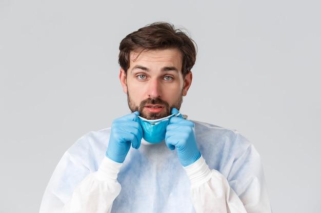 Covid-19, pandemie, gezondheidswerkers die het virus bestrijden. vermoeide en uitgeputte arts die een medisch beademingsapparaat uittrekt, handschoenen, vermoeidheid voelt voor het werken in de nachtploeg in het ziekenhuis met coronaviruspatiënten.