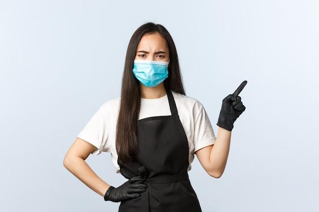 Covid-19 pandemie, sociale afstand, kleine bedrijven en het voorkomen van virusconcept. sceptisch fronsend aziatisch cafépersoneel, barista met medisch masker en handschoenen die rechterbovenhoek wijzen met veroordeling