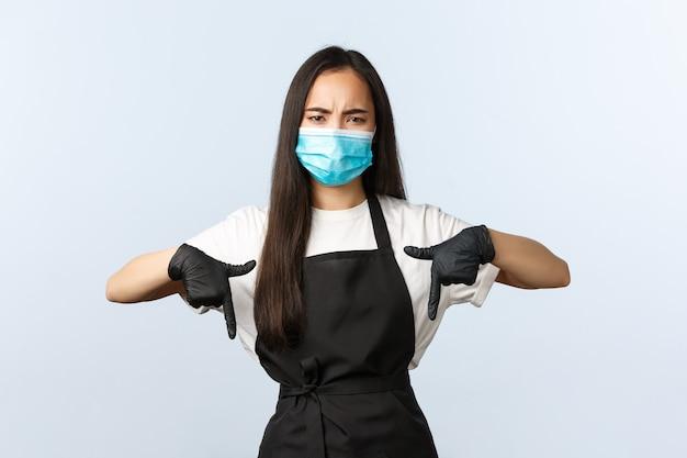 Covid-19 pandemie, sociale afstand, kleine bedrijven en het voorkomen van virusconcept. teleurgestelde fronsende aziatische werknemer, serveerster met medisch masker en handschoenen die naar beneden wijzen.