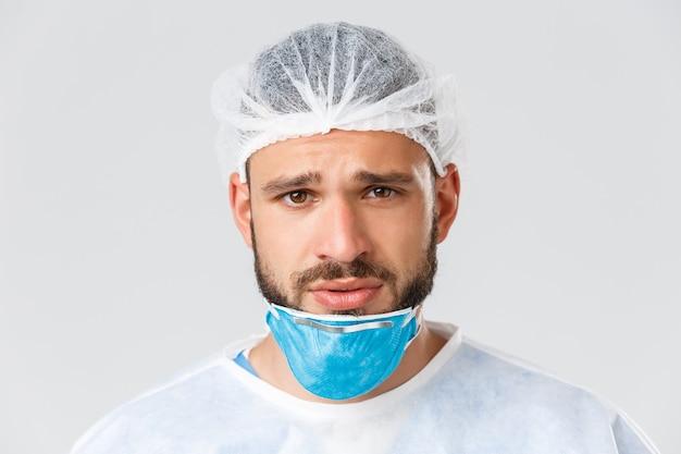 Covid-19 pandemie, virusuitbraak, kliniek en gezondheidswerkers concept. close-up van het uitgeputte ademhalingsapparaat van de dokter en kijk camera moe, vechtend tegen een pandemie van het coronavirus