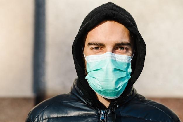 Covid-19 pandemisch coronavirus. jonge mens in stadsstraat die gezichtsmasker draagt beschermend voor het verspreiden van ziekte covid-19. sluit omhoog van de mens met chirurgisch masker op gezicht tegen sars-cov-2.