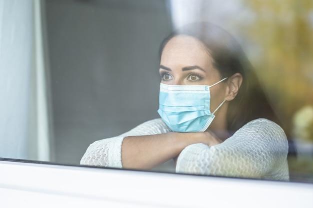 Covid-19 pandemische depressie veroorzaakt door sociaal isolement tijdens een quarantaine door een gezichtsmasker met een vrouw.