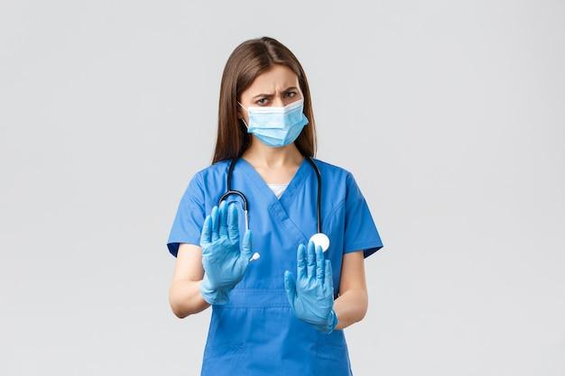 Covid-19, preventie van virus, gezondheid, gezondheidswerkers concept. nee, dank u. ontevreden en onwillige vrouwelijke verpleegster of arts in medisch masker en scrubs, stop, afwijzing of weigering ondertekenen