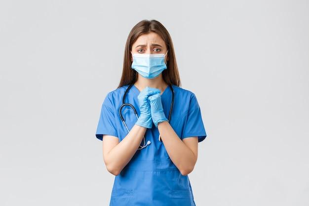 Covid-19, preventie van virus, gezondheid, gezondheidswerkers en quarantaineconcept. hoopvolle wanhopige vrouwelijke verpleegster in blauwe scrubs die mensen smeekt om thuis te blijven tijdens pandemische coronavirus, hand in hand in gebed