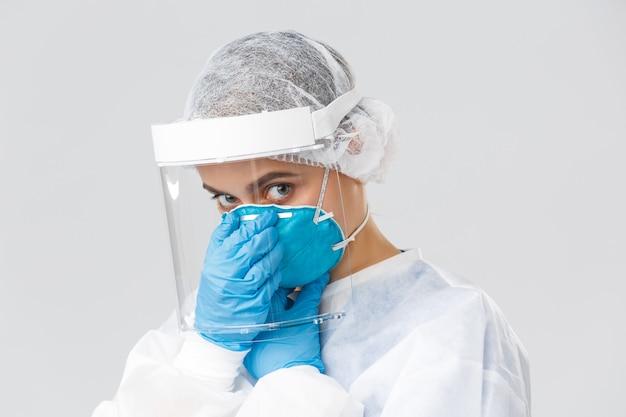 Covid-19, preventie van virus, gezondheid, gezondheidswerkers en quarantaineconcept. jonge arts die het coronavirus bestrijdt, met zieke patiënten werkt in persoonlijke beschermingsmiddelen, een gezichtsmasker aanbrengt
