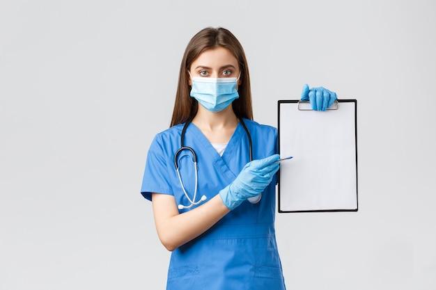 Covid-19, preventie van virus, gezondheid, gezondheidswerkers en quarantaineconcept. serieus uitziende vrouwelijke verpleegster of arts in blauwe scrubs schrijft medicijnen voor, wijzend naar papier op klembord