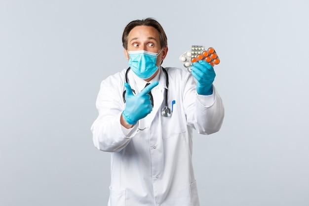 Covid-19, preventie van virussen, gezondheidswerkers en vaccinatieconcept. opgewonden arts met medisch masker en handschoenen die met de vinger naar de geneeskunde wijzen, medicatie tonen, pillen aanbevelen