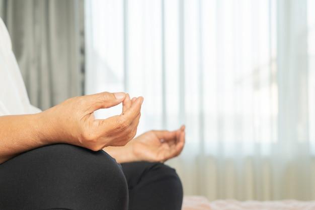 Covid-19 quarantaineactiviteit voor oudere vrouwen die mediteren, blijven thuis om risico's te vermijden