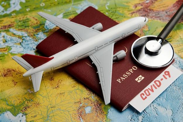 Covid 19-reisdocument op de achtergrond van de wereldkaart met paspoort en medische stethoscoop. coronavirus pandemie reisconcept. covid-19 medische test