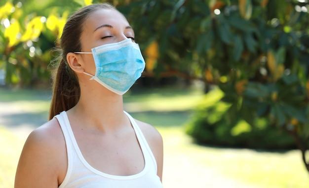 Covid-19 sluit omhoog van jonge sportieve vrouw met chirurgisch masker die in het park ademen