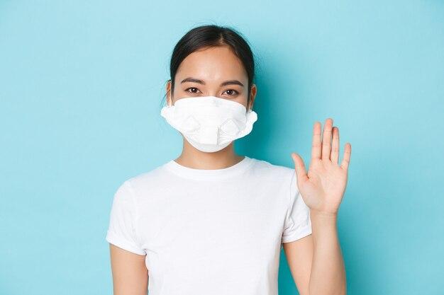 Covid-19, sociaal distantiëren en coronavirus pandemie concept. vriendelijk glimlachend aziatisch meisje in gasmasker dat hallo zegt, iemand welkom heet, persoon begroet met zwaaiende hand, lichtblauwe muur