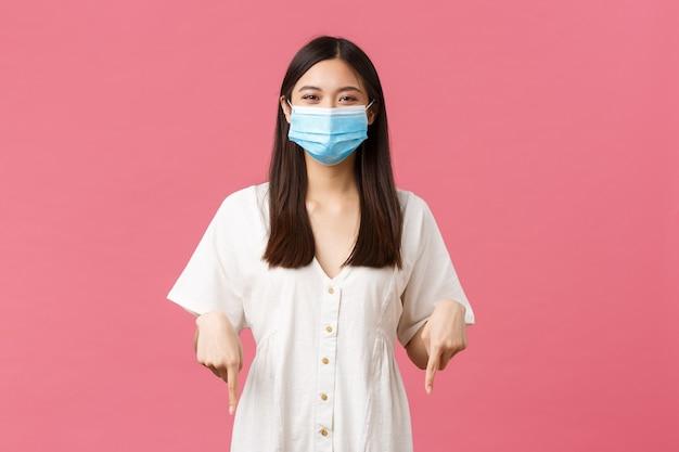 Covid-19, social distancing, virus en lifestyle concept. opgetogen schattig meisje met medisch masker en witte jurk, grappig bordje lezend, tevreden vingers naar beneden wijzend, glimlachend over roze achtergrond