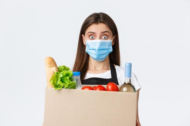 Covid-19 sociale afstand, bezorging en boodschappen doen tijdens het coronavirusconcept. jonge aangename verkoopster, kassier in medisch masker die over boodschappen naar de klant handelt