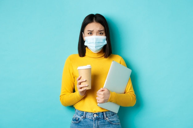 Covid-19, sociale afstand en pandemisch concept. bezorgde aziatische vrouw met medisch masker, verdrietig fronsend, laptop vasthoudend voor werk en kopje koffie