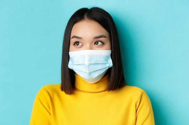 Covid-19, sociale afstand en pandemisch concept. headshot van schattige aziatische vrouw met kort donker haar en medisch masker, naar links kijkend, staande over blauwe achtergrond