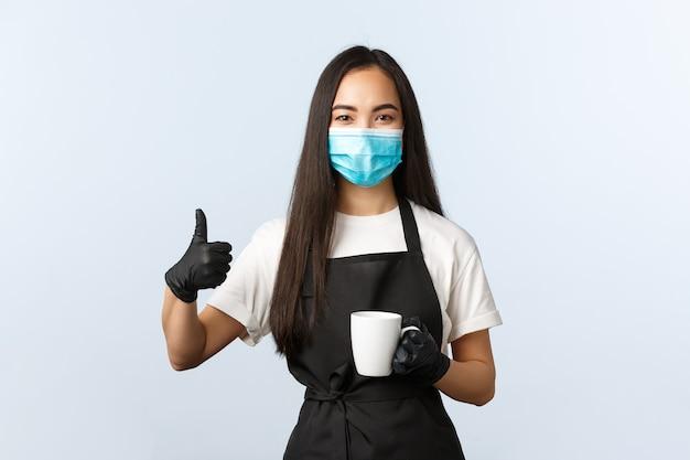 Covid-19, sociale afstand, kleine coffeeshopzaken en het voorkomen van virusconcept. glimlachende knappe aziatische vrouwelijke barista in medisch masker toont duim omhoog als het overhandigen van mok met lekker drankje.