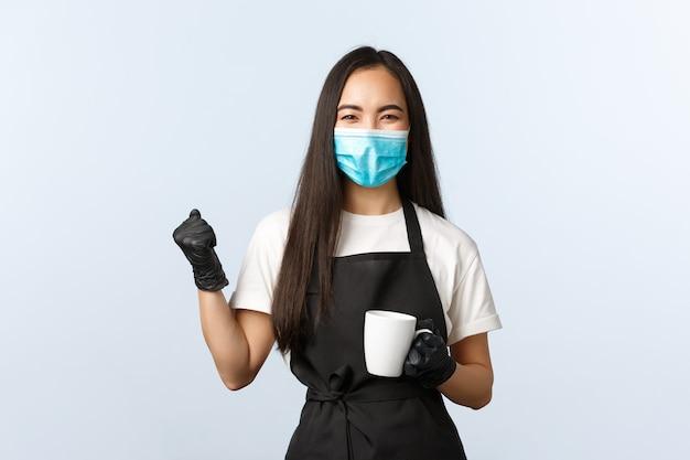 Covid-19, sociale afstand, kleine coffeeshopzaken en het voorkomen van virusconcept. meisje maakte eindelijk heerlijke koffie en begon te werken in café, vuistpomp, vreugde, mok met drankje vasthoudend.