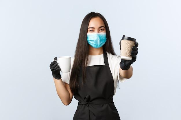 Covid-19, sociale afstand, kleine coffeeshopzaken en het voorkomen van virusconcept. schattige lachende aziatische barista raadt aan om tijdens het coronavirus afhaalbekers te gebruiken en je te laten drinken.
