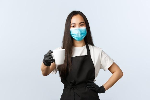 Covid-19, sociale afstand, kleine coffeeshopzaken en het voorkomen van virusconcept. vriendelijk lachende aziatische vrouwelijke barista die je bestelling overhandigt, bezoekersmok met drankje geeft, medisch masker draagt.