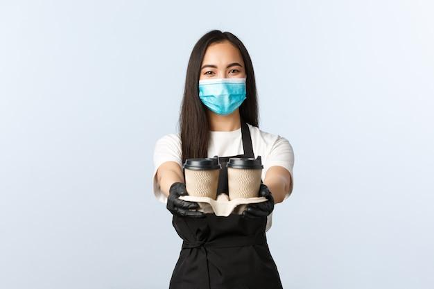 Covid-19, sociale afstand, kleine coffeeshopzaken en het voorkomen van virusconcept. vriendelijke aangename aziatische serveerster, café-barista in medisch masker die koffie serveert, bestelling overhandigt met afhaalbekers
