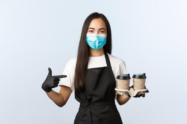 Covid-19, sociale afstand, kleine coffeeshopzaken en het voorkomen van virusconcept. vrolijke aziatische barista, vrouwelijke café-eigenaar die de bestelling serveert, wijzend op kopjes met koffie of thee, medisch masker dragen.
