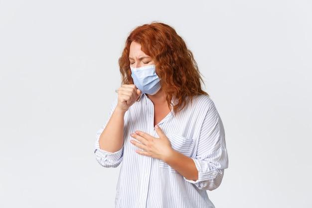 Covid-19 sociale afstand nemen, coronavirus zelfquarantaine en mensenconcept. zieke roodharige vrouw van middelbare leeftijd die hoest, een medisch masker draagt, een zure keel heeft, ziektesymptomen, griep oploopt.
