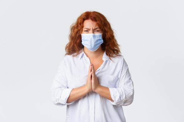 Covid-19 sociale afstand nemen, maatregelen ter voorkoming van coronavirus en mensenconcept. hoopvolle bezorgde vrouw van middelbare leeftijd in medisch masker, vrouw met rood haar die om hulp smeekt en om gunst pleit.