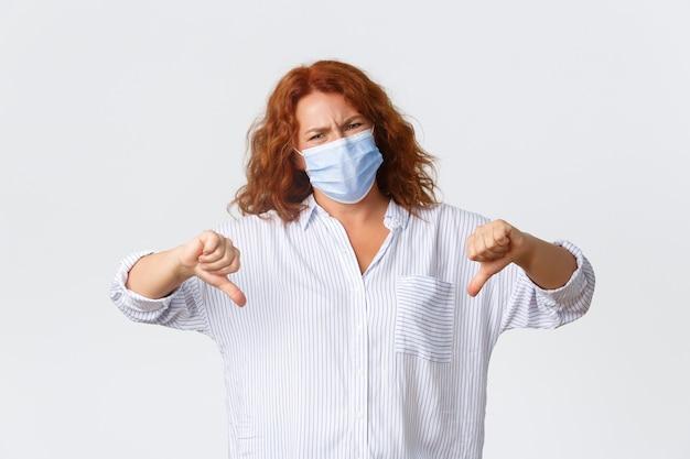 Covid-19 sociale afstand nemen, maatregelen ter voorkoming van coronavirus en mensenconcept. ontevreden en boos roodharige vrouw op middelbare leeftijd die thumbs-down teleurstelling toont, die medisch masker draagt.