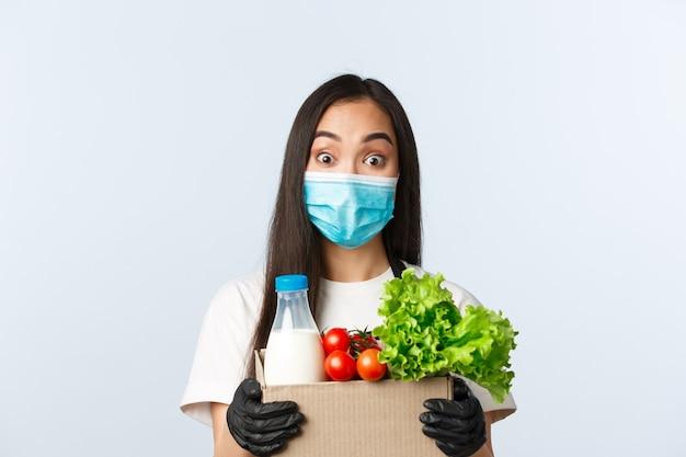 Covid-19, supermarkt, werkgelegenheid, klein bedrijf een viruspreventieconcept. vrolijke schattige aziatische winkelmedewerker, kassier met medisch masker en handschoenen die afhaalbestelling van de klant geven