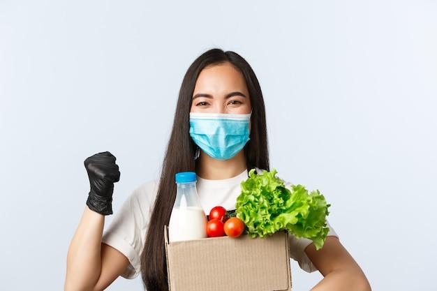 Covid-19, supermarkt, werkgelegenheid, klein bedrijf en virusconcept. enthousiaste aziatische vrouwelijke werknemer, winkelkassier met medisch masker, vuistpomp moedigt aan om veilig te kopen, tas met boodschappen te geven