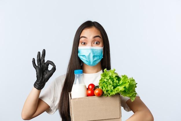 Covid-19, supermarkt, werkgelegenheid, klein bedrijf en virusconcept. enthousiaste, schattige aziatische winkelmedewerker die je online bestelling inpakt, slecht houdt met boodschappen en goed laat zien, medisch masker draagt