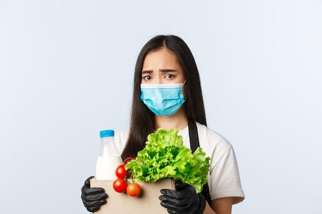 Covid-19, supermarkt, werkgelegenheid, kleine bedrijven en het voorkomen van virusconcept. bezorgde en overstuur fronsende aziatische vrouwelijke winkelmedewerker, kassier in medisch masker met boodschappentas.