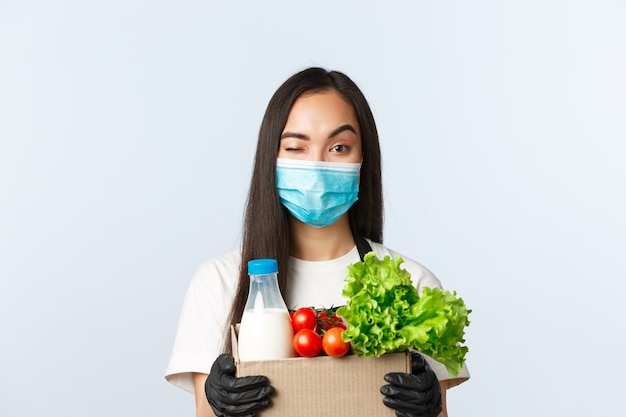 Covid-19, supermarkt, werkgelegenheid, kleine bedrijven en het voorkomen van virusconcept. glimlachende aziatische vrouwelijke winkelmanager, kassier met medisch masker en handschoenen, die voor uw etensbestelling zorgt.