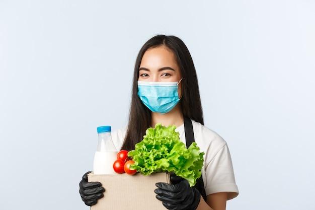 Covid-19, supermarkt, werkgelegenheid, kleine bedrijven en het voorkomen van virusconcept. glimlachende schattige aziatische vrouwelijke winkelmedewerker, kassier met medisch masker en handschoenen die voor uw boodschappenbestelling zorgen.