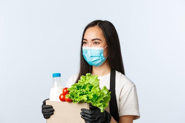 Covid-19, supermarkt, werkgelegenheid, kleine bedrijven en het voorkomen van virusconcept. glimlachende vriendelijke aziatische winkelmedewerker, kassier die de bestelling overhandigt aan de klant, medisch masker en handschoenen draagt