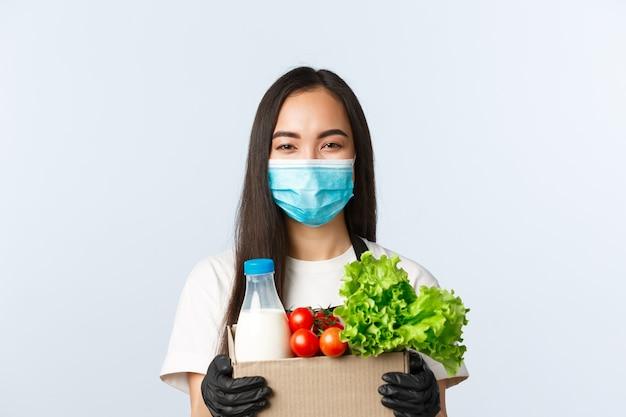 Covid-19, supermarkt, werkgelegenheid, kleine bedrijven en het voorkomen van virusconcept. vrolijk lachende aziatische kassier, winkelmedewerker met medisch masker en handschoenen die producten in zak houden