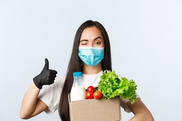 Covid-19, supermarkt, werkgelegenheid, kleine bedrijven en het voorkomen van virusconcept. vrolijke winkelmedewerker, kassier met medisch masker en handschoenen zorgen voor veilig winkelen tijdens coronavirus, duim omhoog