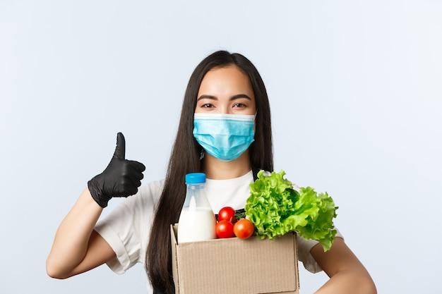 Covid-19, supermarkt, werkgelegenheid, kleine bedrijven en het voorkomen van virusconcept. zelfverzekerde en vrolijke winkelmedewerker, kassier met medisch masker en handschoenen zorgen voor veilig winkelen tijdens het coronavirus.