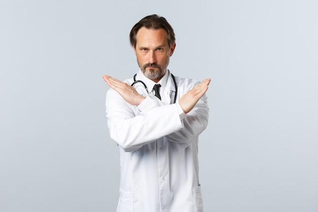 Covid-19, uitbraak van coronavirus, gezondheidswerkers en pandemisch concept. ernstige ontevreden mannelijke arts in witte jas, handen kruisen om stopgebaar te tonen, iets verbieden of verbieden