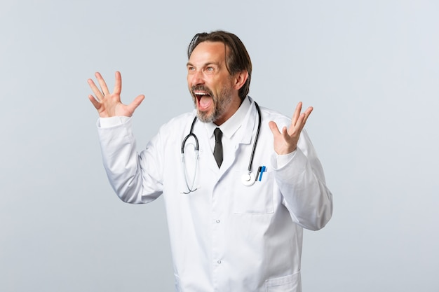 Covid-19, uitbraak van coronavirus, gezondheidswerkers en pandemisch concept. gekke gekke dokter in witte jas gebarend, confronterend werknemer in kliniek, boos gebarend en links woedend