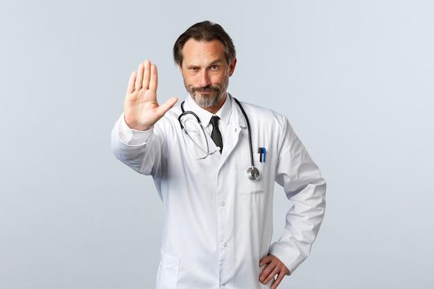 Covid-19, uitbraak van coronavirus, gezondheidswerkers en pandemisch concept. ontevreden serieuze arts in witte jas, strek arm uit om stopbord te tonen, uitbrander of waarschuwing, actie afkeuren