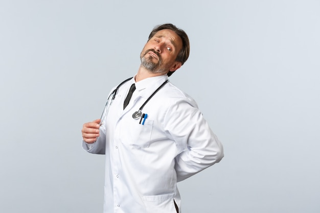 Covid-19, uitbraak van coronavirus, gezondheidswerkers en pandemisch concept. verontruste mannelijke arts van middelbare leeftijd die zich uitgeput voelt na nachtdienst in de kliniek met zieke patiënten, verstuikte rug.