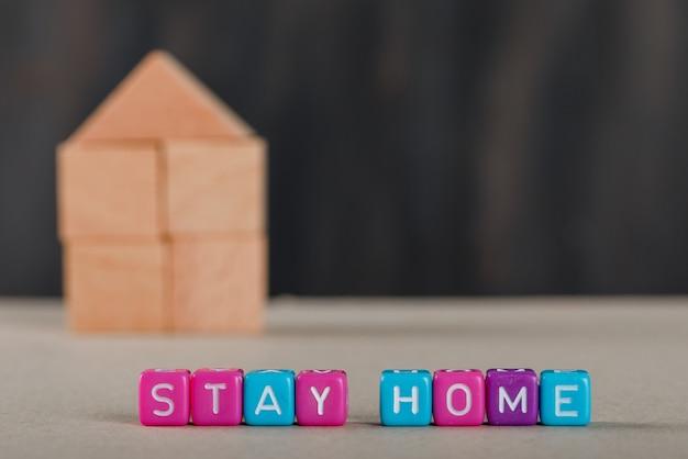 Covid-19 uitbraakadviesconcept met houten huis, gekleurde blokjes